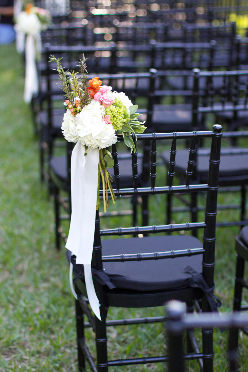 Elegant black chairs were adorned with clusters of hydrangea, roses, berries, renunculus, and rosemary sprigs!