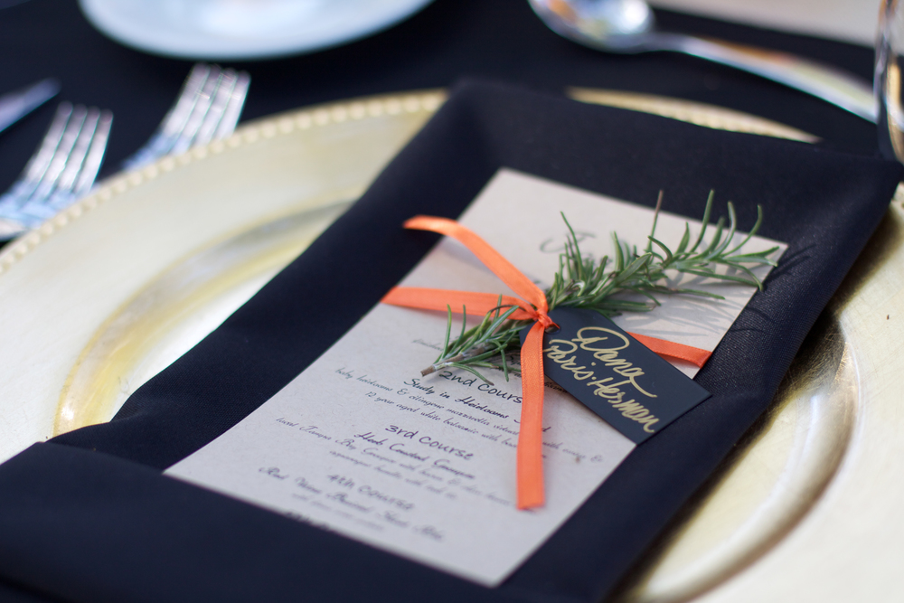 Sprigs of rosemary and slate place cards were tied to kraft menu cards at each place setting