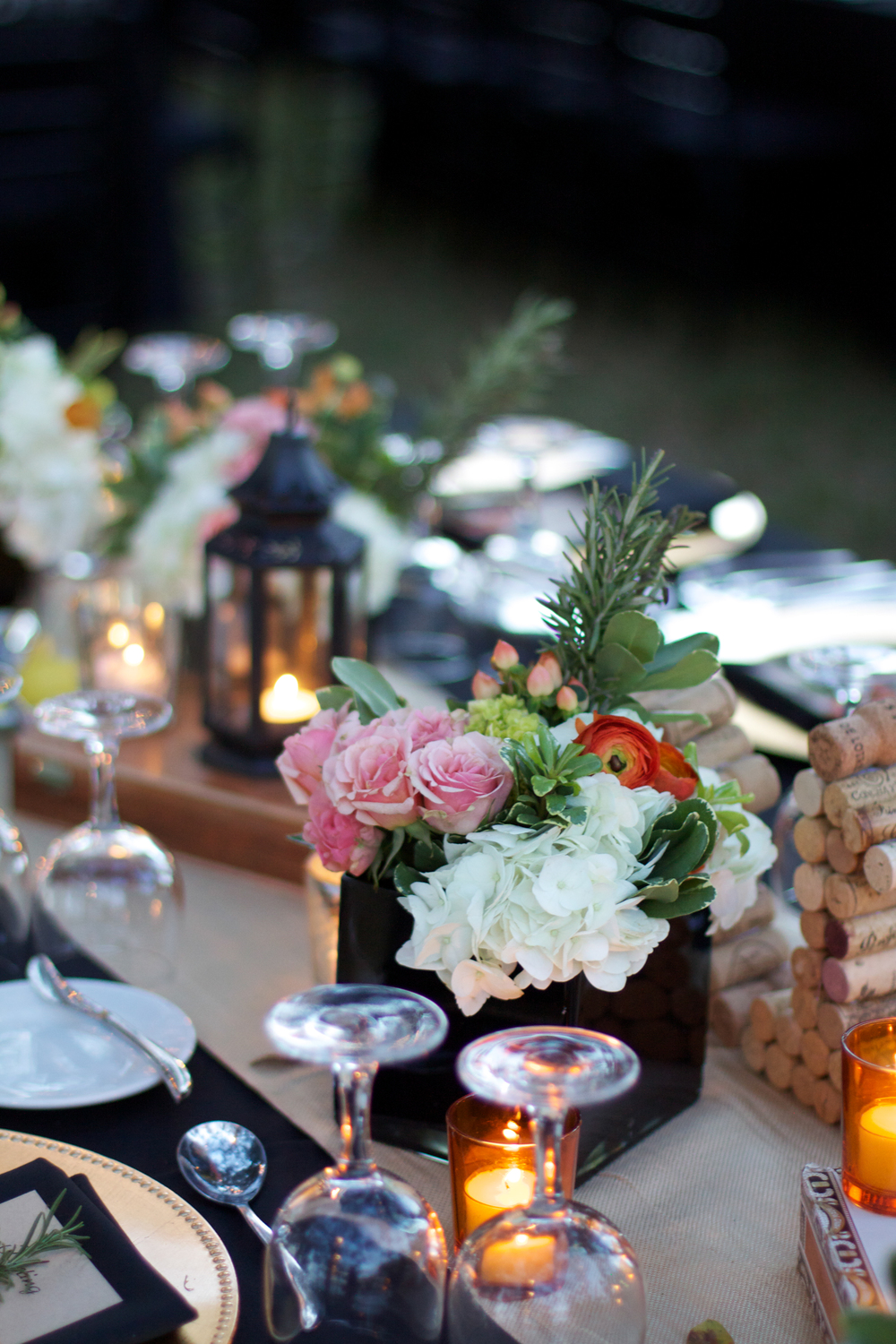 Centerpieces featured collections of cigar boxes, lanterns, candles, and onyx vases of fresh flowers