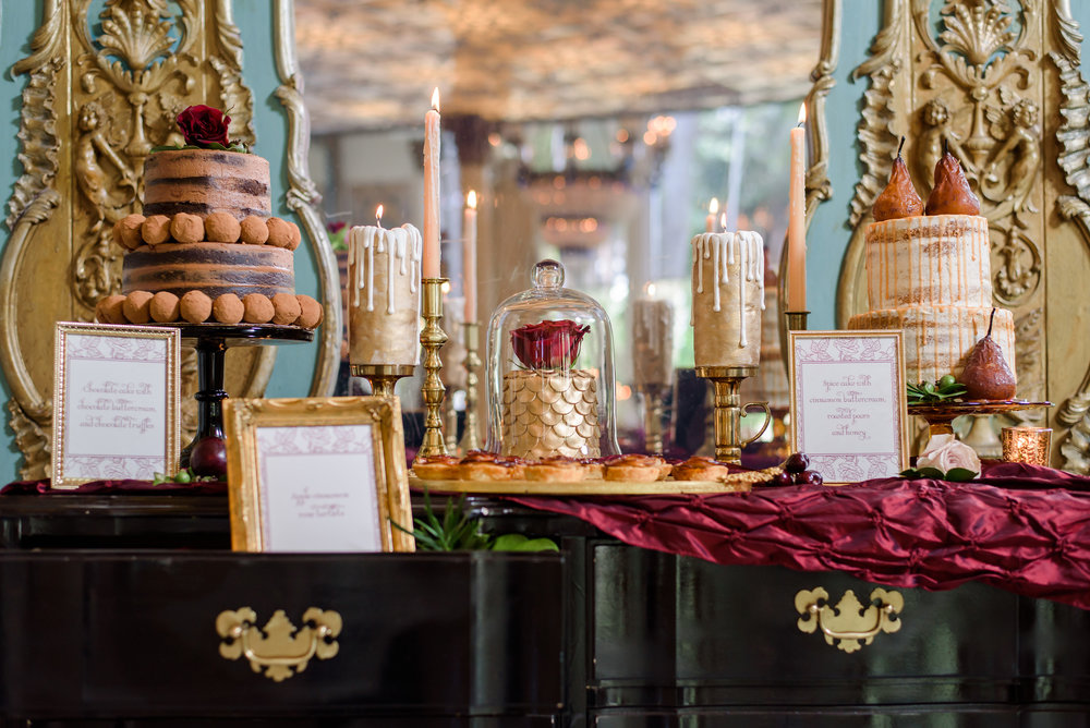 The elaborate dessert display included a cloche covered cake, apple-rosette tarts, and decadent frosted cakes.