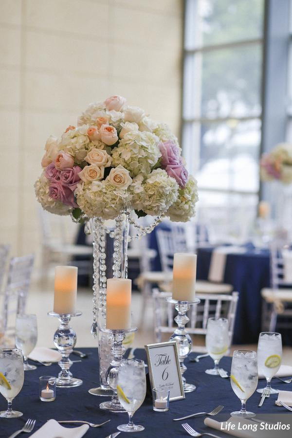 Centerpieces included tall hydrangea and rose arrangements, accented by crystals and candles