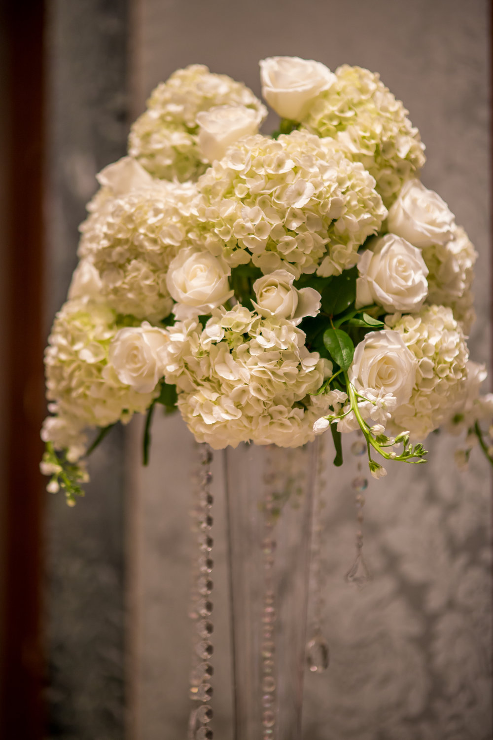 Pilsner vases dripping with crystals were topped with arrangements of hydrangea, roses, and stock.
