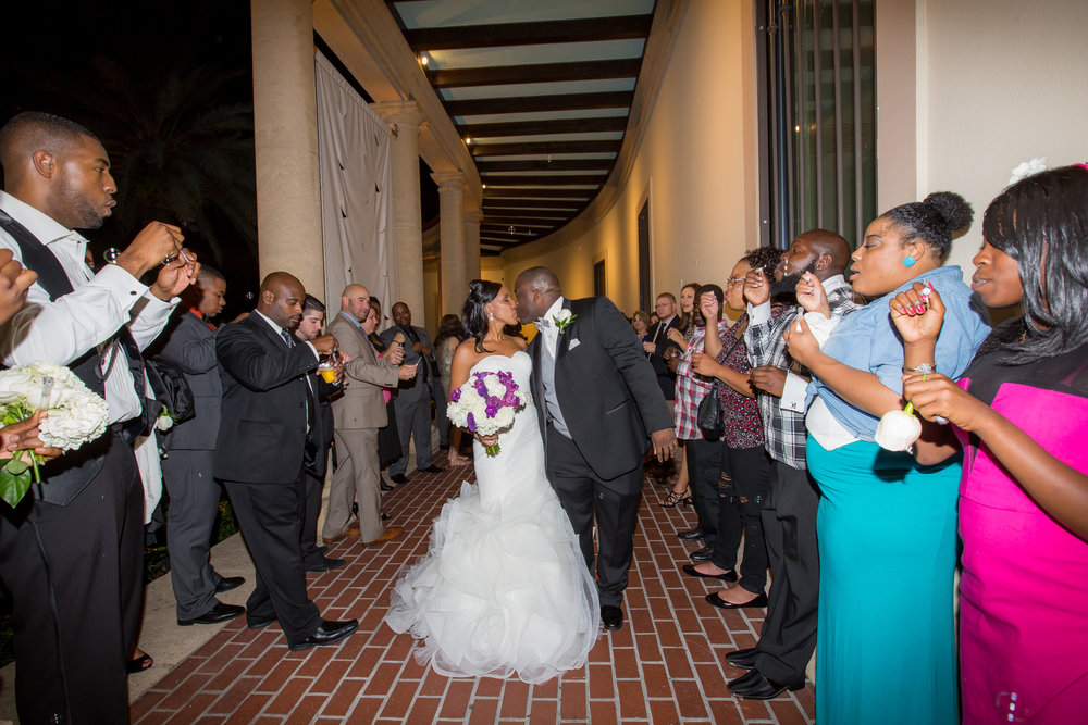 Guests sent off the bride and groom through a path of bubbles along the museum veranda.