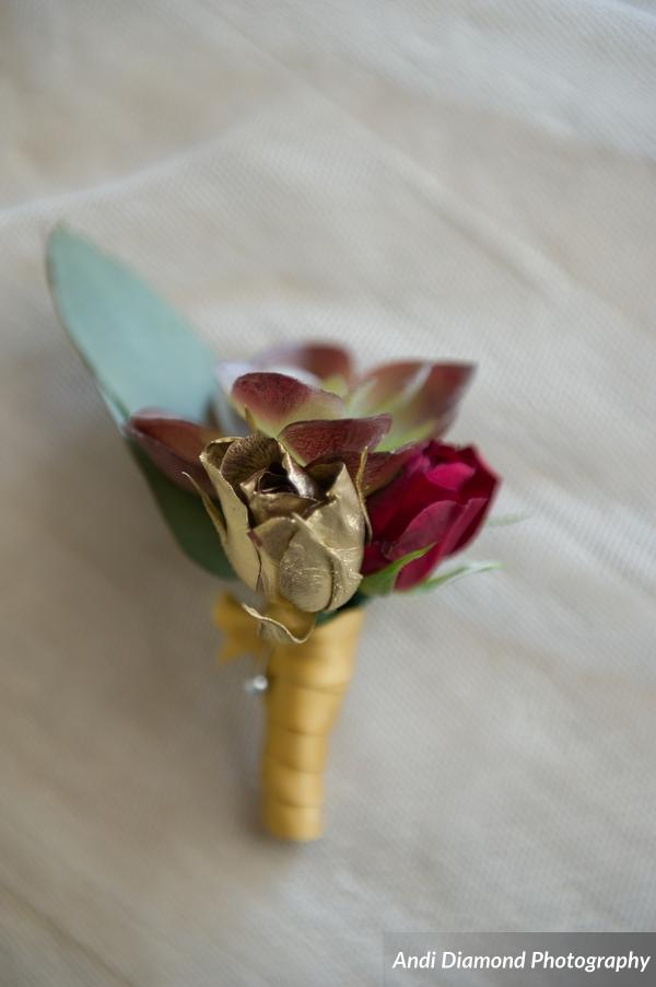 The groom's boutonniere featured a succulent accented by gold and deep red tea roses.