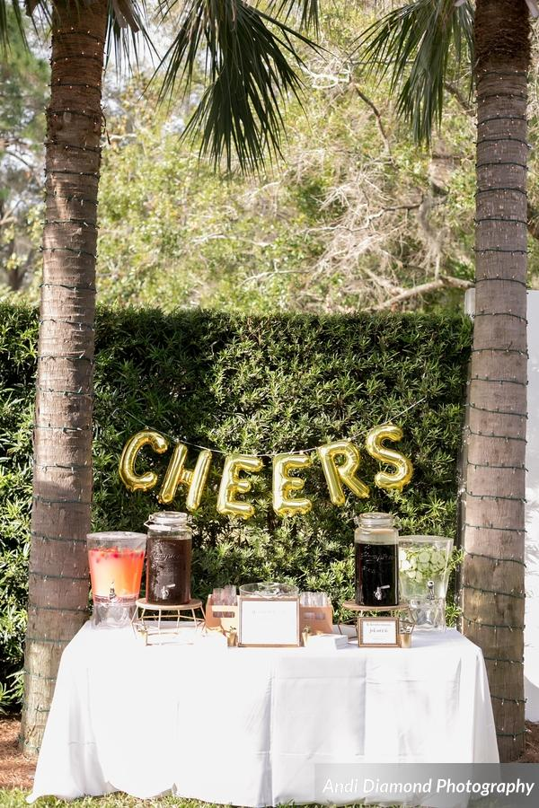 A beverage station with CHEERS balloons offered dispenser of strawberry lemonade, cucumber water, and classic Jack & Coke as the groom's signature drink.
