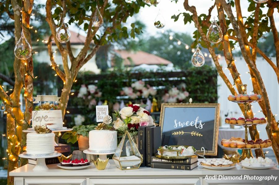 Gold-painted succulents could be found in details such as suspended orbs over the dessert display, the bride's bouquet and updo, and accenting the pennant-style cake toppers.