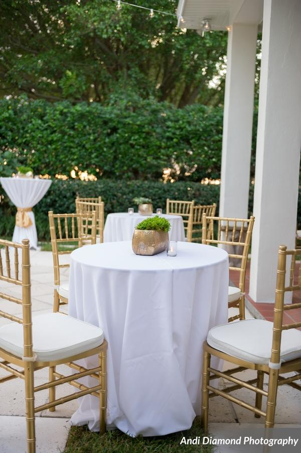 Tables around the pool deck featured gold ceramic pots filled with ivy and fern.