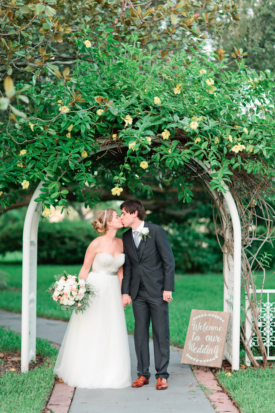 The couple posed beneath the entrance trellis, blooming with a floral vine.