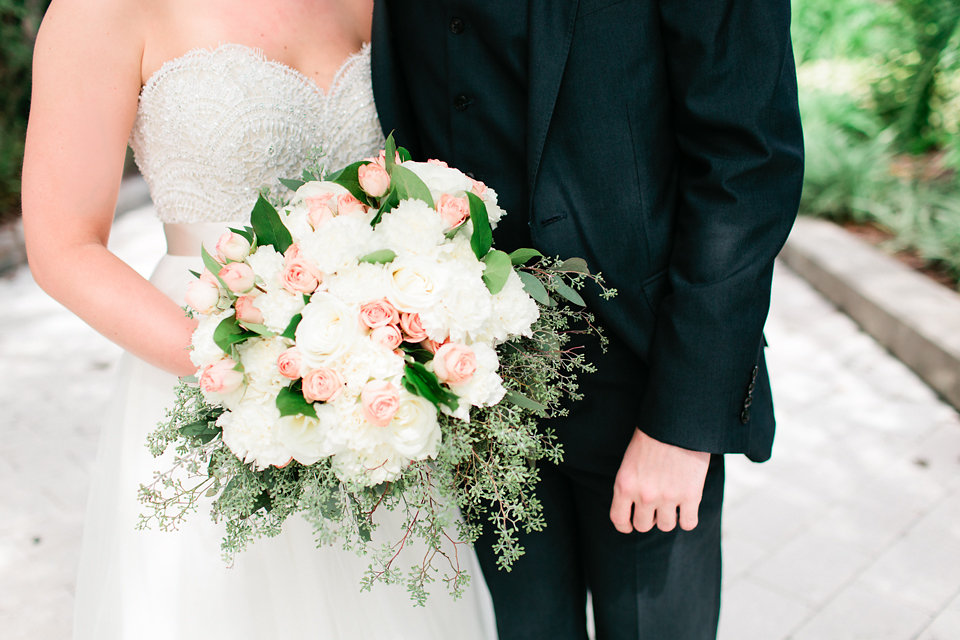 The bride's loose garden-style bouquet included fluffy white hydrangea, white and blush roses, vibrant green leaves, and a collar of eucalyptus.