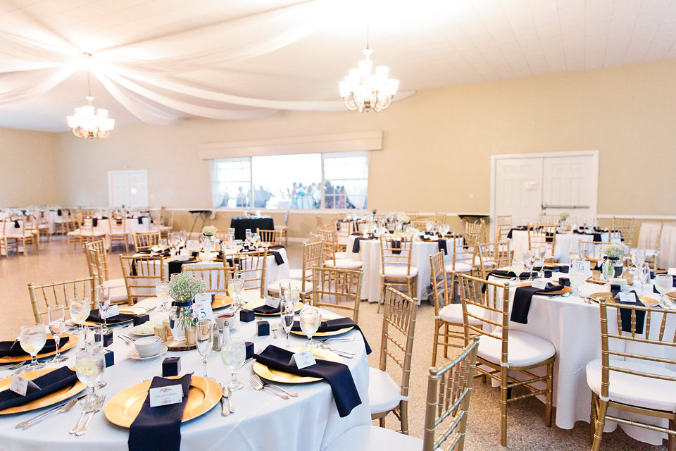 The reception details included chic chiavari chairs, metallic chargers, and billowy ceiling draping.