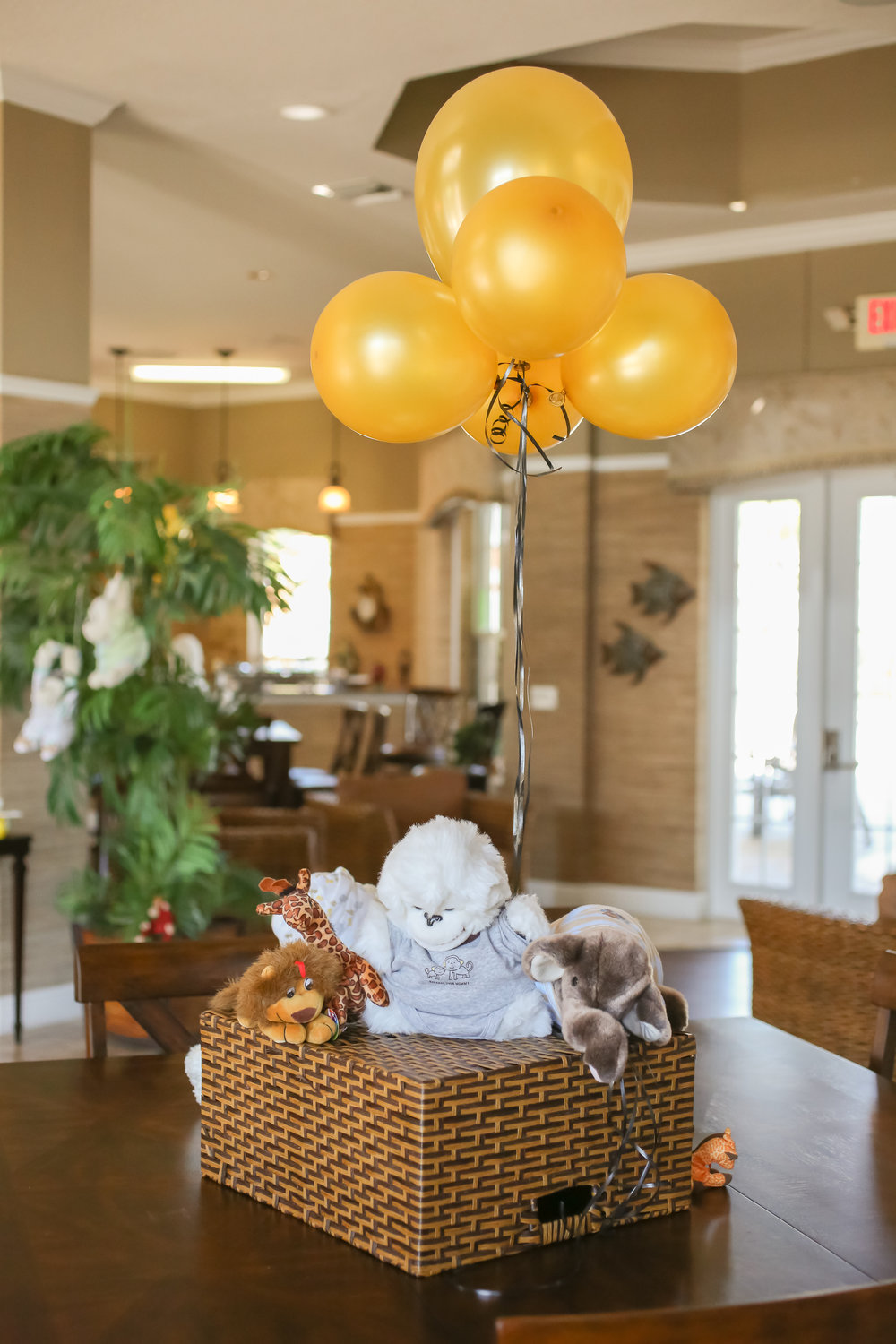 Inside, tables were decorated with assorted jungle animal toys dressed in baby clothes and holding gold balloons (all meant for baby to enjoy after the shower!)