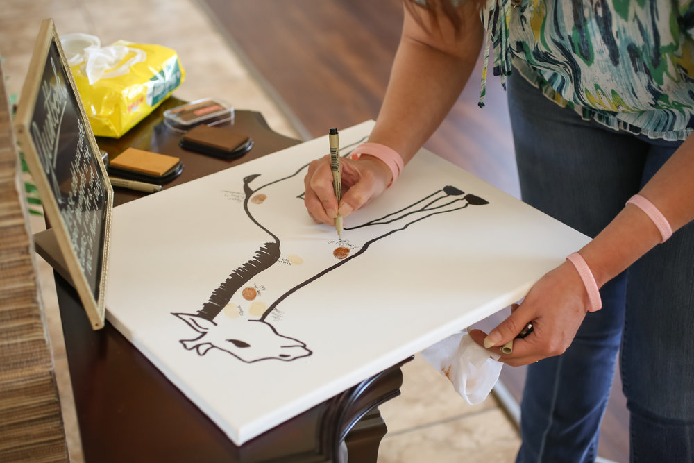 As a unique keepsake to document all those in attendance, guests stamped their fingerprints onto a giraffe silhouette canvas and wrote their names next to the fingerprint spots.