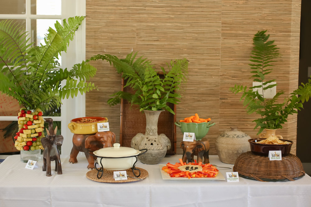 Jungle themed tent cards boasting food items like Cub Crudites, Tiger Tails, Tropical Fruit Palm, and Forest Foliage adorned the food station.