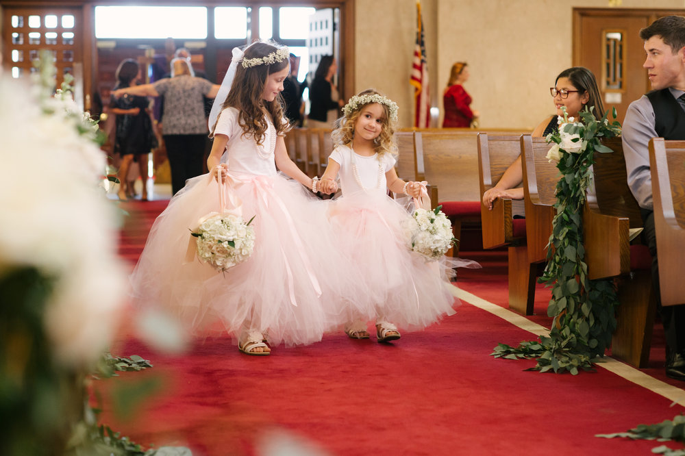 How sweet are the flower girls holding hands down the aisle?!