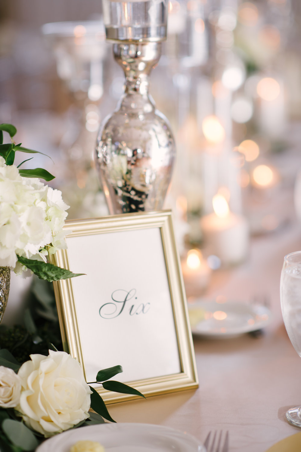 The table numbers, set in an elegant black script within gold frames, sat amongst candlelight reflected off of silver mercury glass accents along the tables.