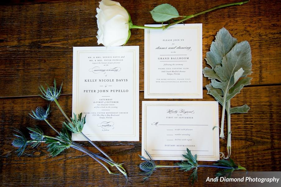 The couple's simple and elegant formal invitation suite with a gilded border, set amongst florals in the colors of their wedding.