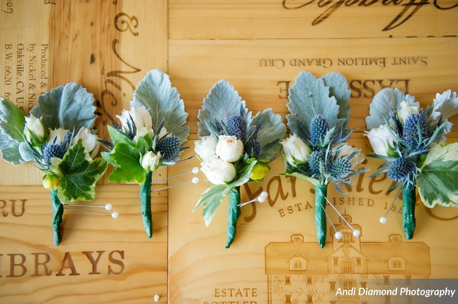 The boutonnieres featured blue thistles with pale blue-green succulent leaves, and adorned with delicate ivory flower buds.