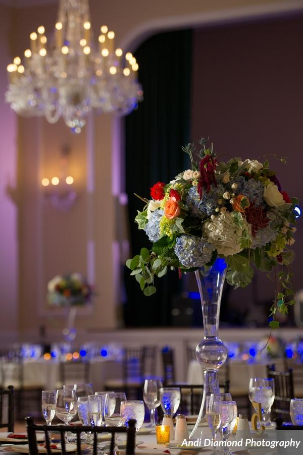 Crystal chandeliers were suspended above tables adorned with organic floral arrangements.