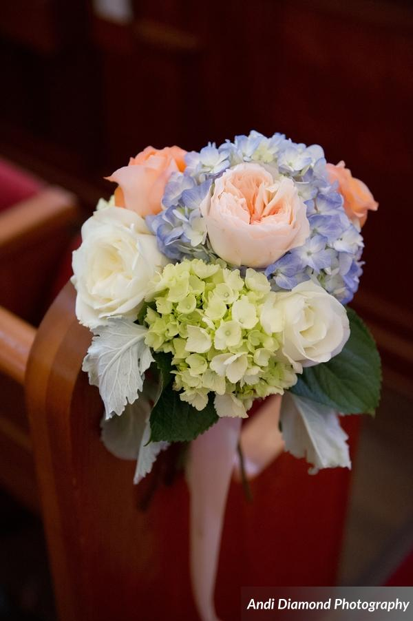 Peachy garden roses, dusty blue hydrangea, ivory roses, and blue-green succulent leaves decorated the ceremony aisle.
