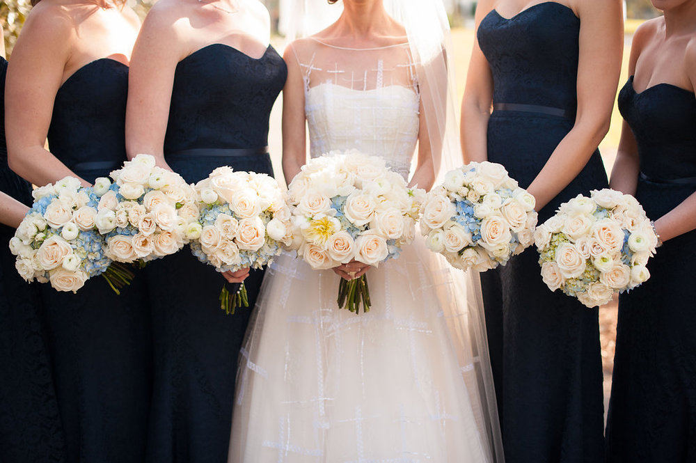 The bride's gown stood out against the bridesmaids strapless navy lace gowns, all accented with bouquets of ivory roses and pops of soft blue hydrangea.