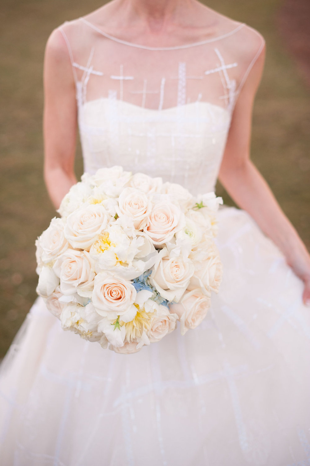 The bride carried a tight, round bouquet full of roses with soft blue hydrangea peeking through.