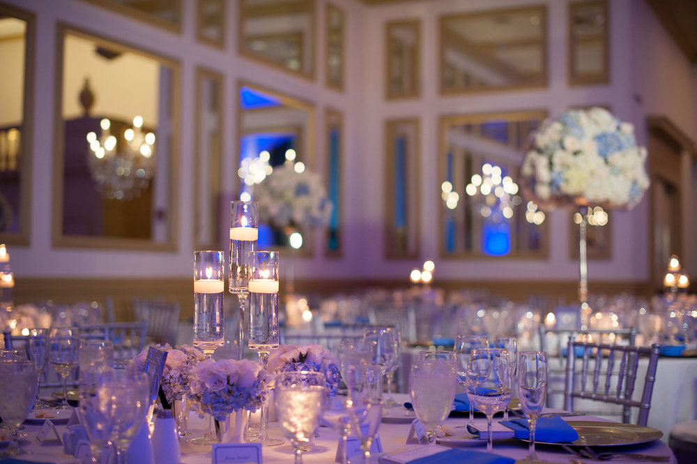 Floating candles and stunning floral arrangements on silver pillars transformed the ballroom into an opulent and romantic affair.