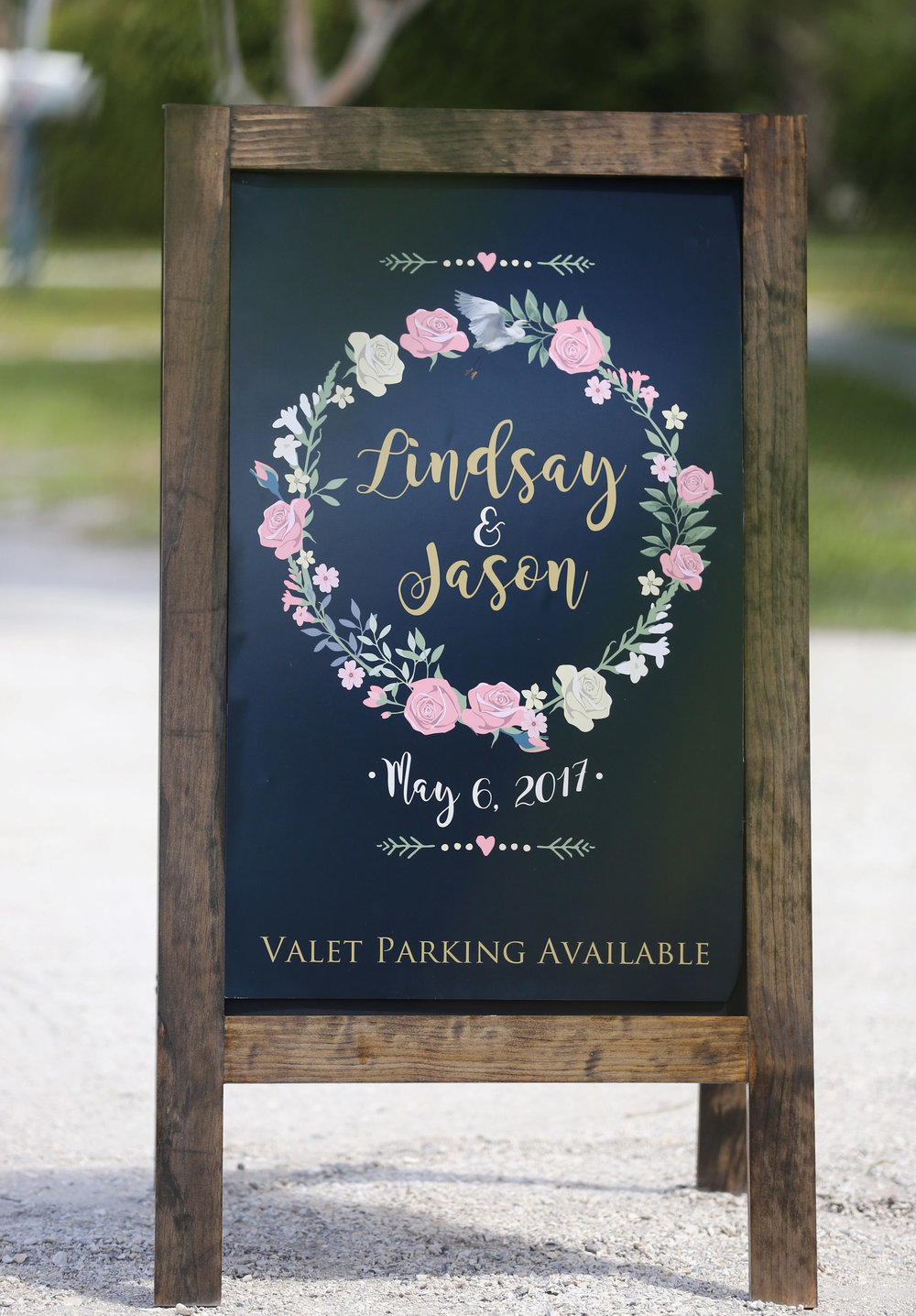 A custom sign with a floral wreath and dark wood frame was created as a welcome sign for guests.