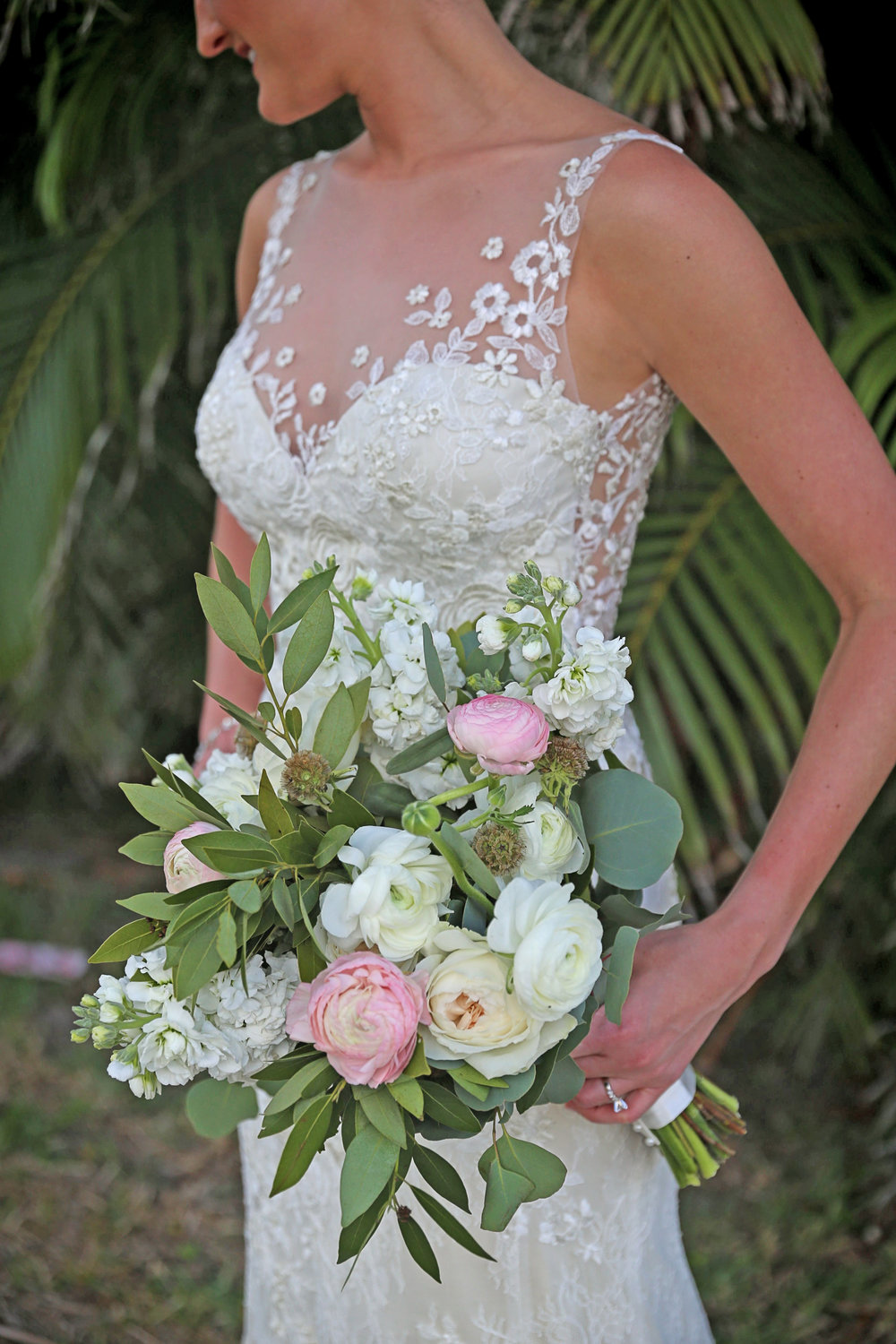 The bride carried a natural bouquet of ivory and pink ranunculus, ivory stalk, and scabiosa, accented with greenery like sage and eucalyptus.