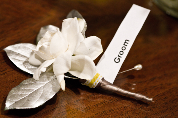 The groom's simple ivory gardenia bloom boutonniere was dressed up with metallic accents.