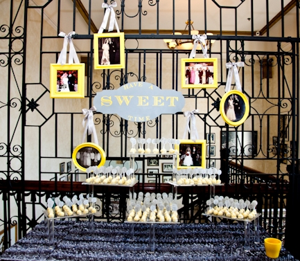 A cake pop escort card display, in the couple's wedding colors, was dressed up with cute signage and family wedding photos.