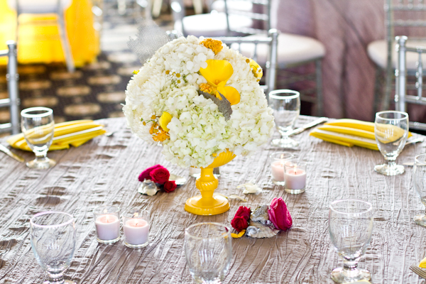 Amidst the grey and yellow color scheme were centerpieces with ivory blooms, little pops of hot pink, and metallic oyster shells!