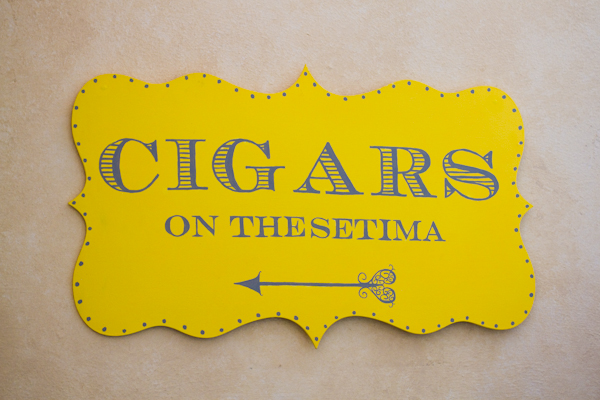 An adorable sign, in the coordinating wedding colors, lead guests to the cigar bar.