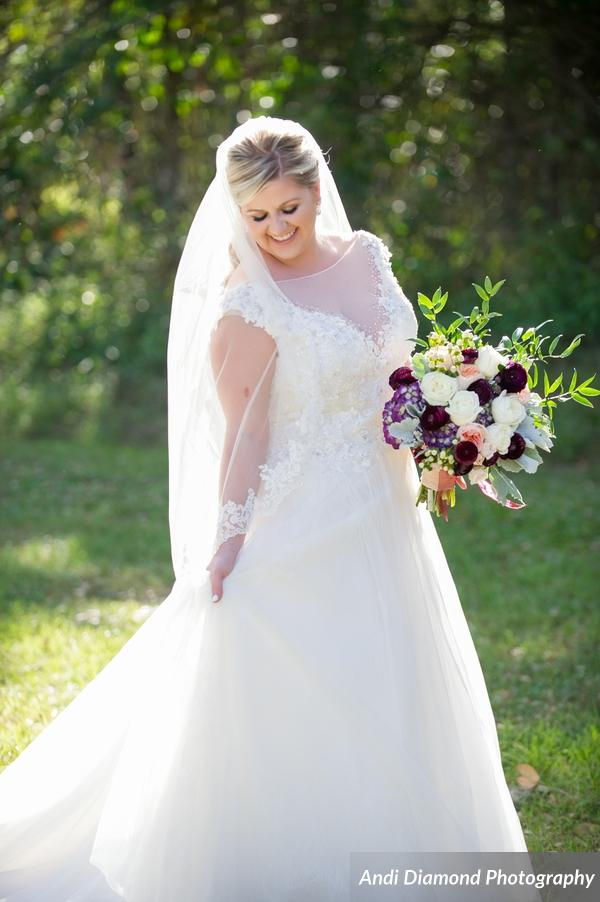 The bride could not look more stunning in her lace and tulle ballgown, complimented by her bouquet of garnet ranunculus, eggplant hydrangea, and ivory and peach garden roses.
