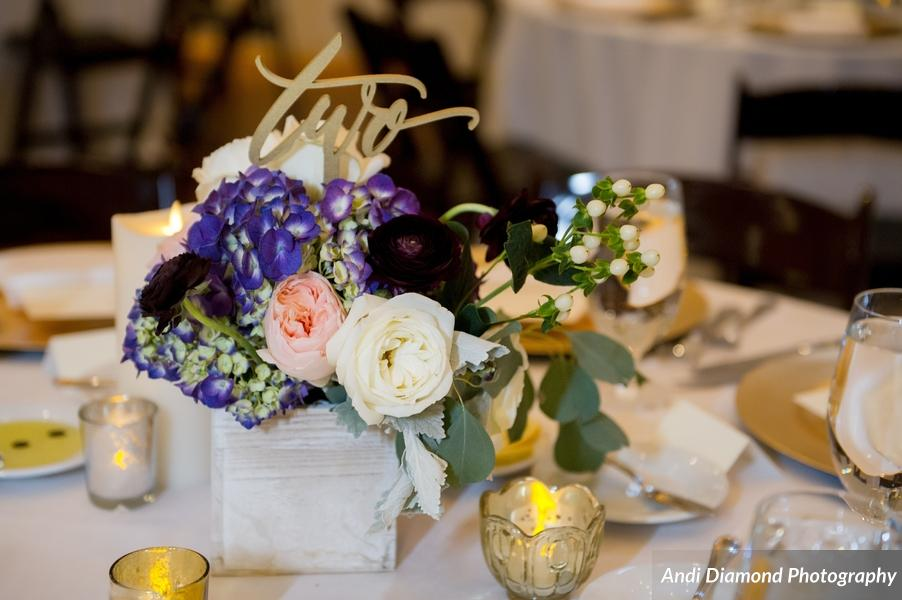 Centerpieces mirrored the bride's bouquet and featured gold table numbers and mercury glass candles.