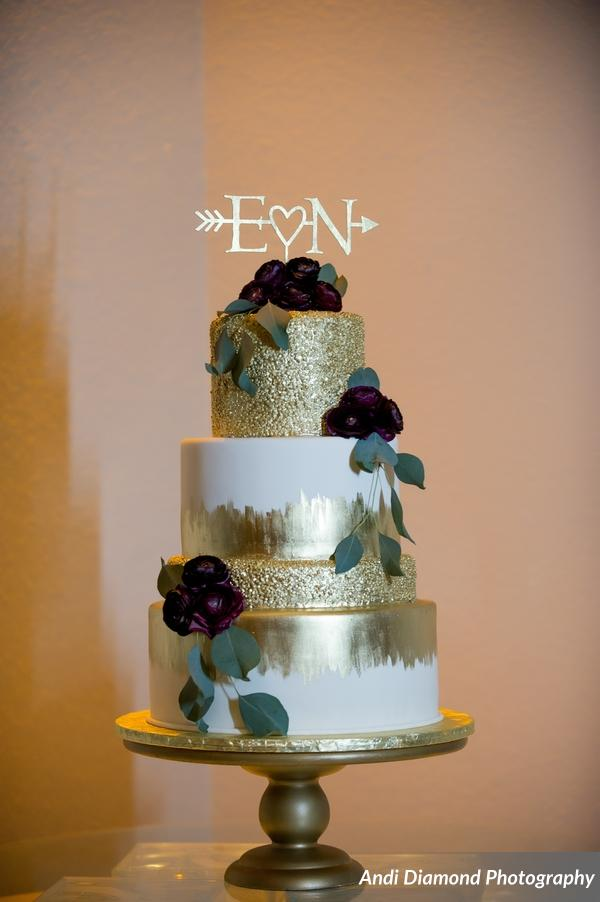 The gorgeous four tiered gold painted cake accented with dark purple flowers, greenery, and the couple's initials.