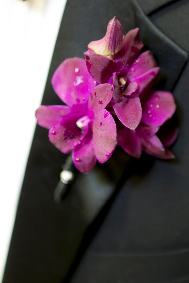 Lush purple orchids were adorned all over this wedding, including the groom's boutonniere.