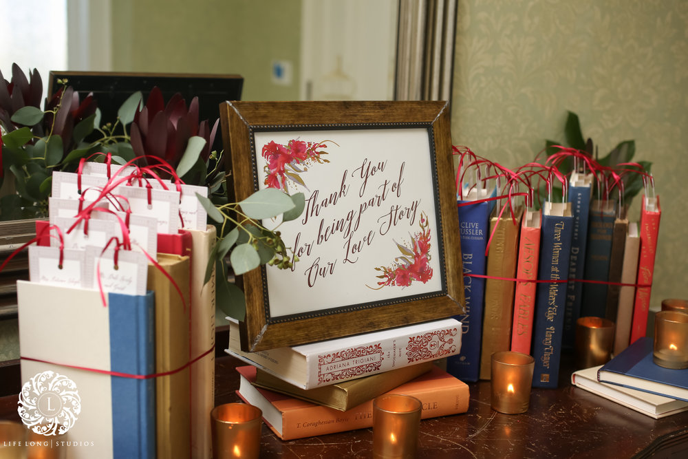 A bookmark escort card display was created with vintage books and a custom sign to celebrate the couple's  love story .