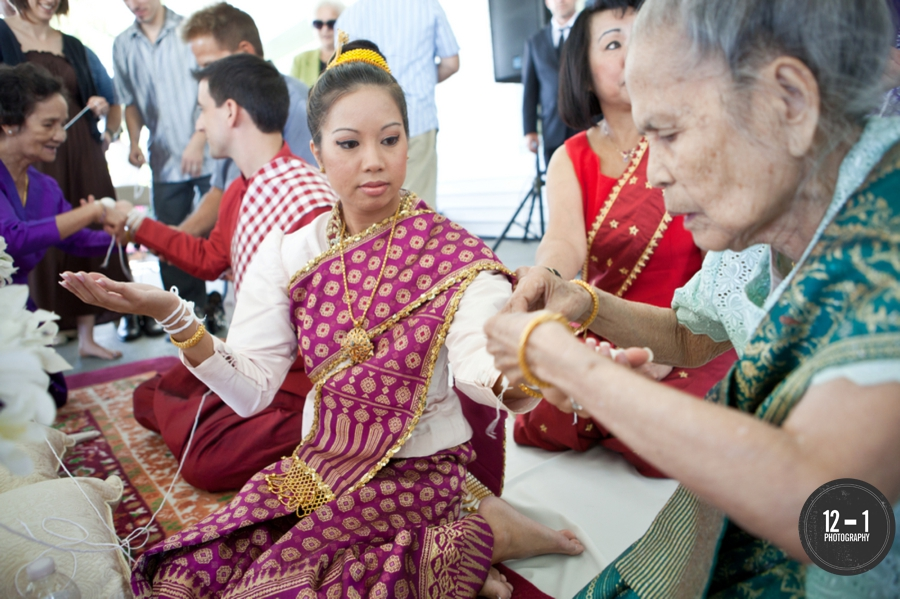 The ceremony featured chanting Buddhist monks, tying white strings to the couple's wrists symbolizing unity, followed by traditional Laotion dancing.