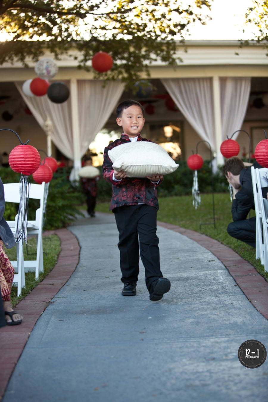 Paper lanterns (that matched with the adorable ring bearers) were strung from oak trees overhead and hung from shepherds hooks along the ceremony aisle.