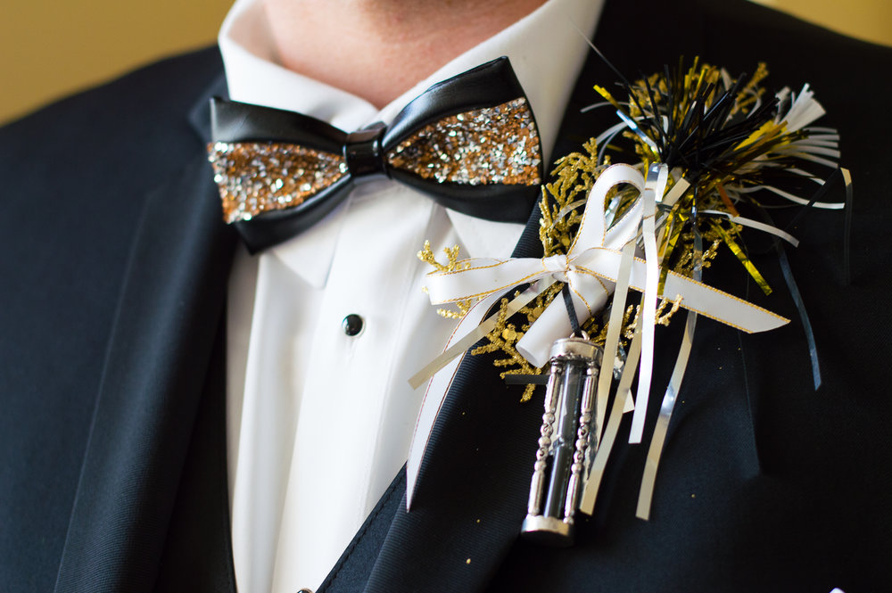 Instead of traditional flowers, ladies carried  bouquets of feathers and glittery floral picks, and guys sported boutonnieres made of party noise makers and hourglasses!