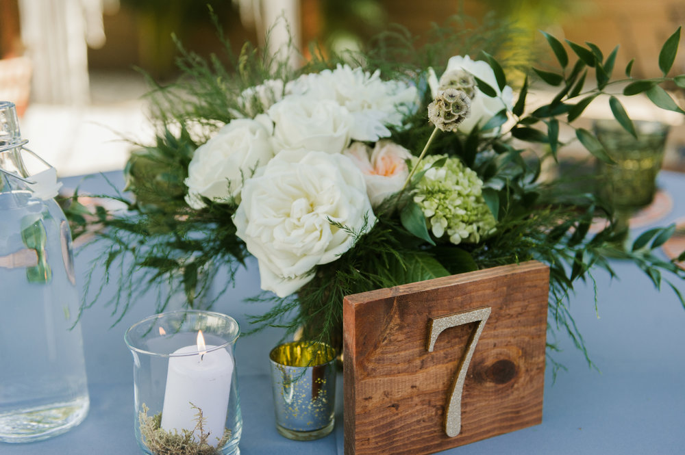 Large blooms and leafy greenery sat at the center of guest tables, adorned with candles set in beds of moss and mercury glass.