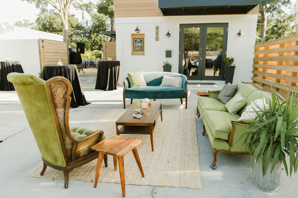 Vintage boho furniture sat outside for guests to relax on during cocktail hour.