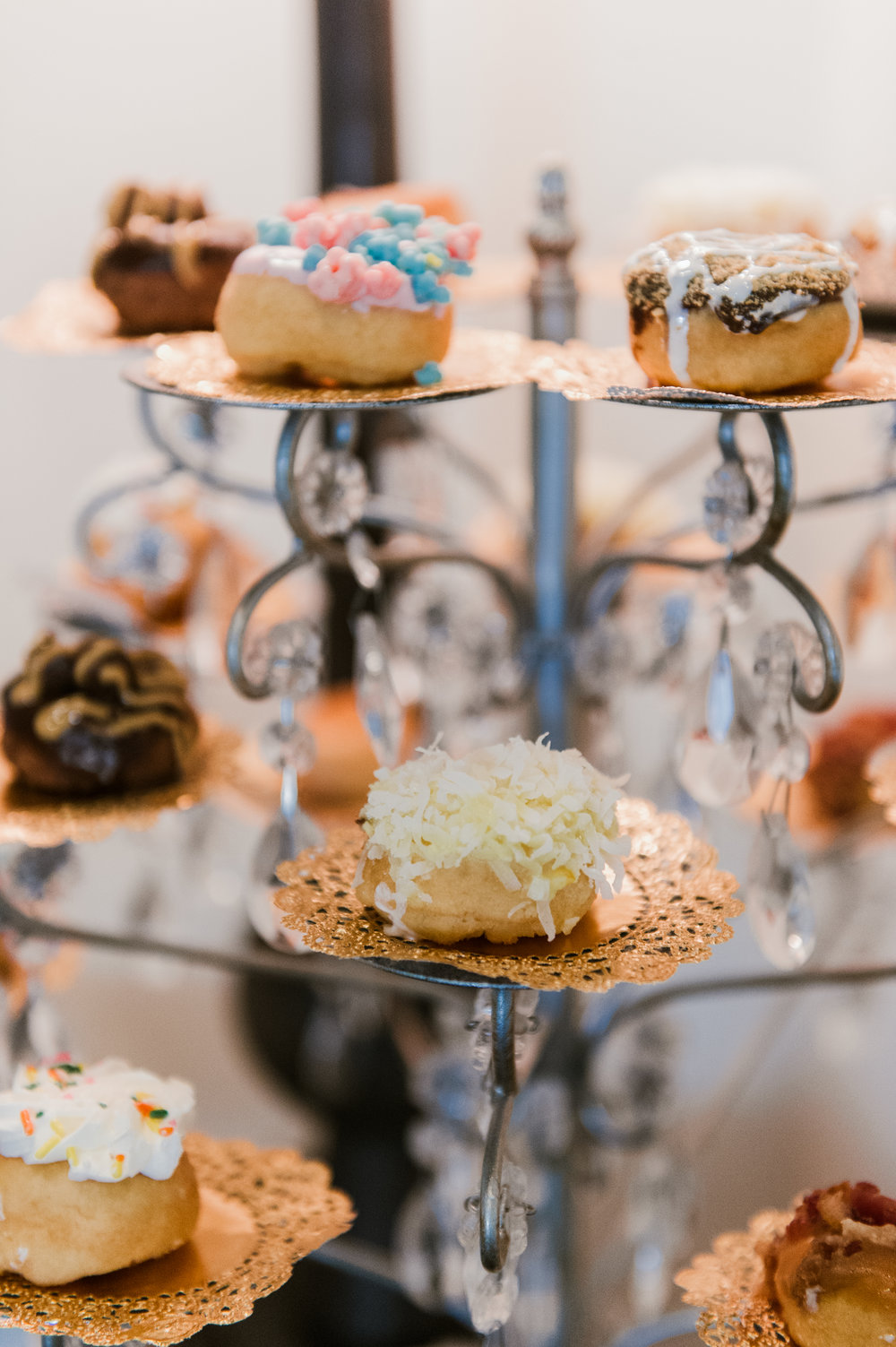 An assortment of mini gourmet donuts served on copper doilies.