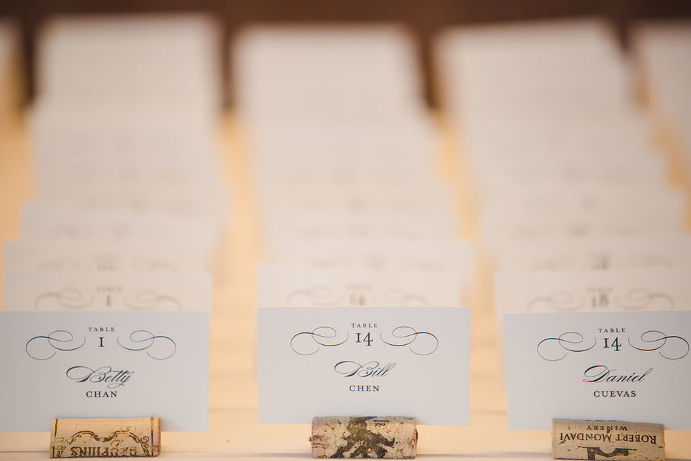 Escort cards with an elegant black script were set into wine bottle corks to guide guests to their seats.