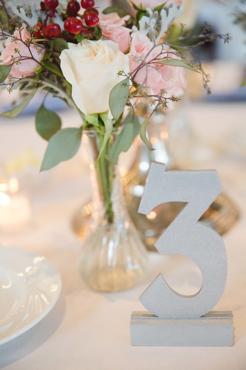 Smaller bunches of florals and sparkling silver table numbers also adorned guest tables.
