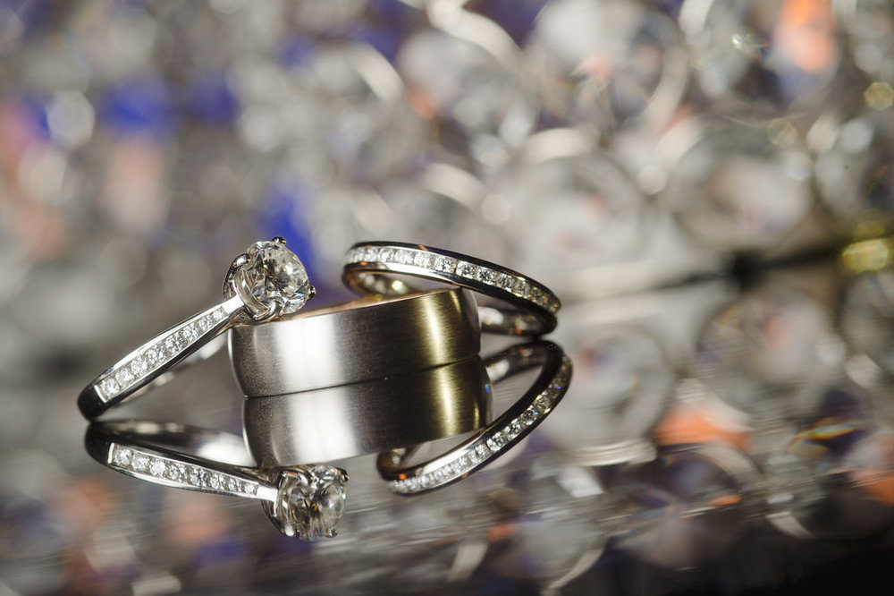 The couple's elegant wedding and engagement rings fit right in with the shimmering silver details of the wedding.