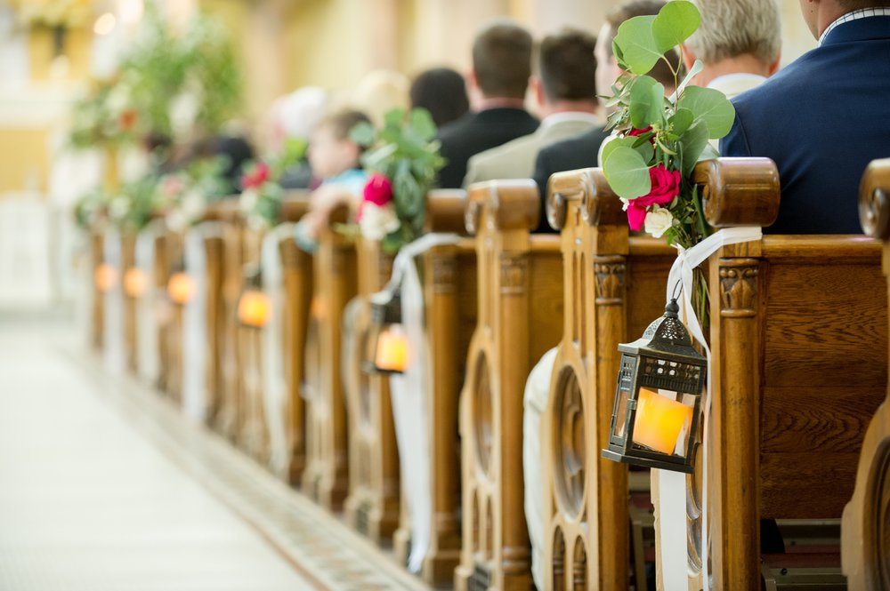 Vintage styled lanterns adorned with greenery and florals lined the ceremony aisle.