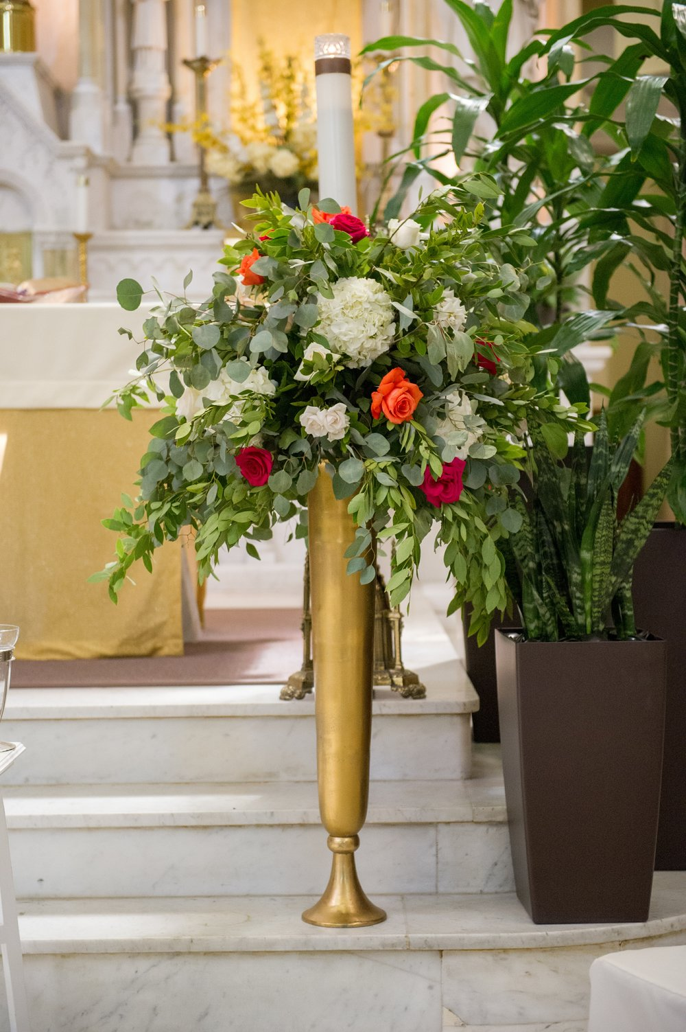 Florals and greenery overflowing in gold pillar vases framed the ceremony space.