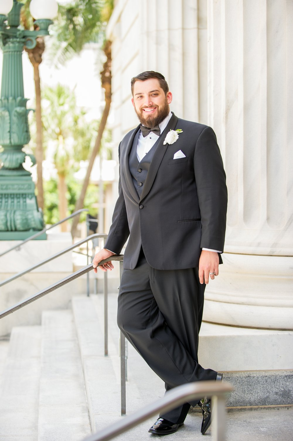 The groom looked sharp in his traditional three-piece black tuxedo, with a simple white floral boutonniere.