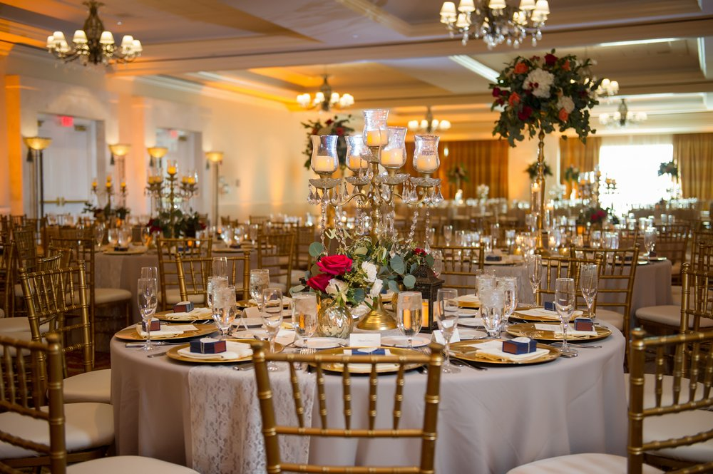 The ballroom tables at The Tampa Marriott Waterside were adorned with lace table runners, gold chargers, gold Chiavari chairs, gold candelabras, and abundant florals in gold vases.